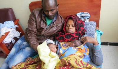 """At a hospital in Ethiopia's capital, Wandamu and his wife Lakish have been in practicing kangaroo care for nearly three weeks. Their heavier, healthier twin, can now sleep on his own and is breast feeding healthily. The smaller twin is still in the """"kangaroo"""" position on his mom's chest."""